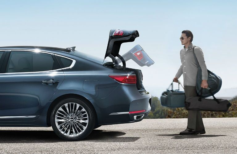 2018 Kia Cadenza exterior drivers side profile with trunk lifting and man behind carrying bags