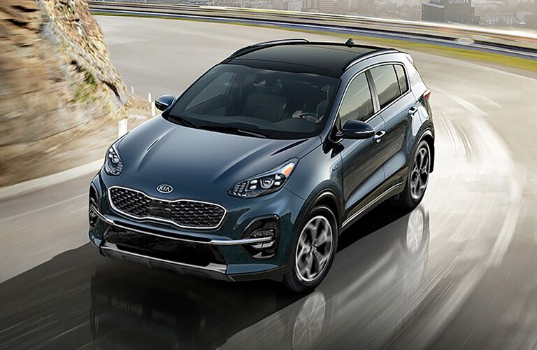 Front view of blue 2020 Kia Sportage on curvy road