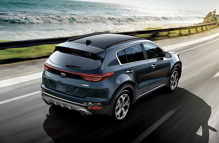 Rear view of blue 2020 Kia Sportage on a road by the sea