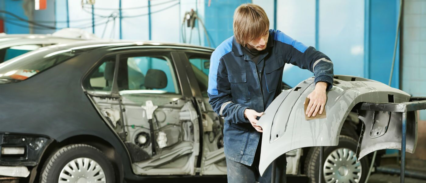 Man repairing door full collision repair body shop
