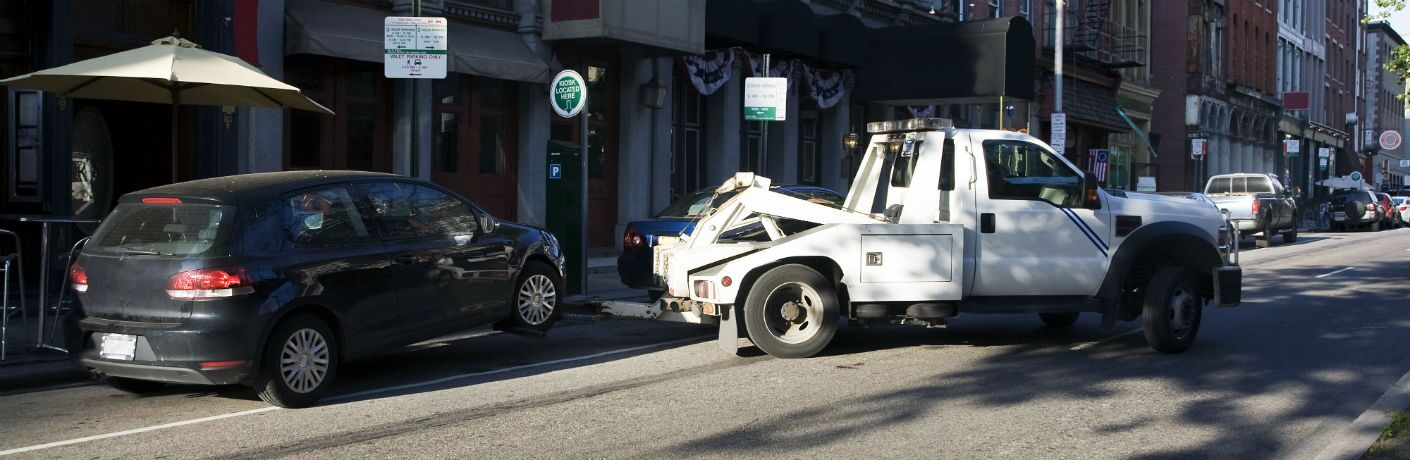 White tow truck towing a black hatchback vehicle