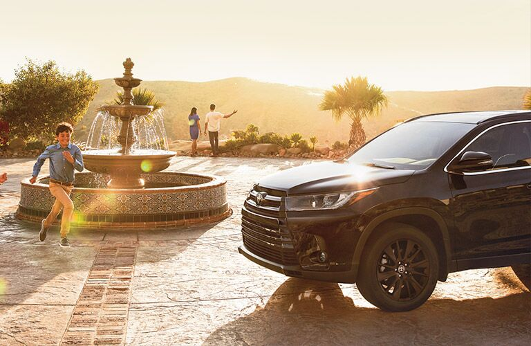 2019 Toyota Highlander black with black rims by a fountain