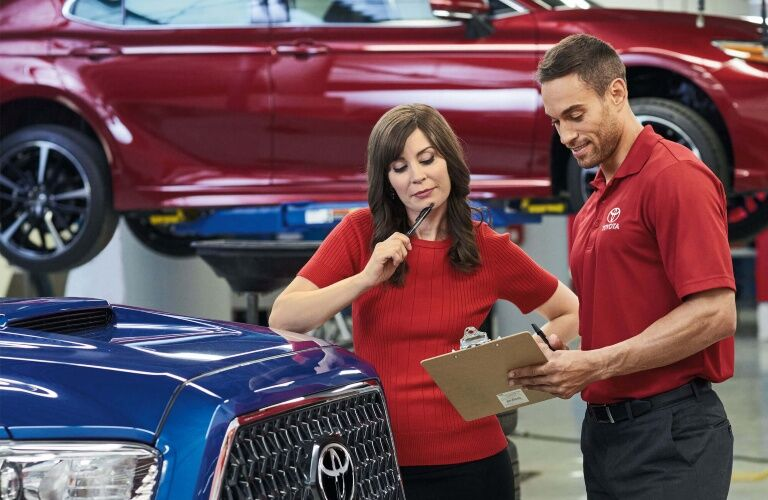 Man and woman talking in front of a Toyota
