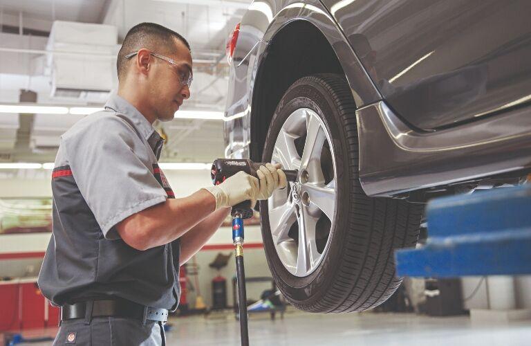 Technician removing car's wheel