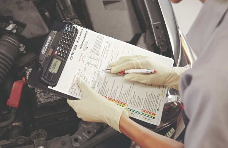 Toyota tech filling out a multi-point inspection form