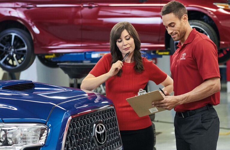 Woman looking over a clipboard list in front of a Toyota
