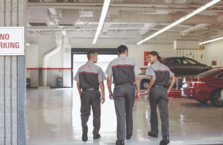 three Toyota employees walking in garage