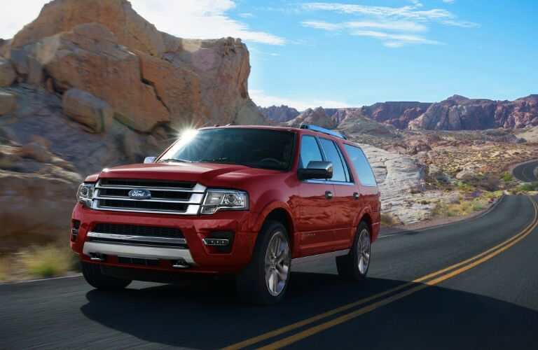Red 2017 Ford Expedition driving along road