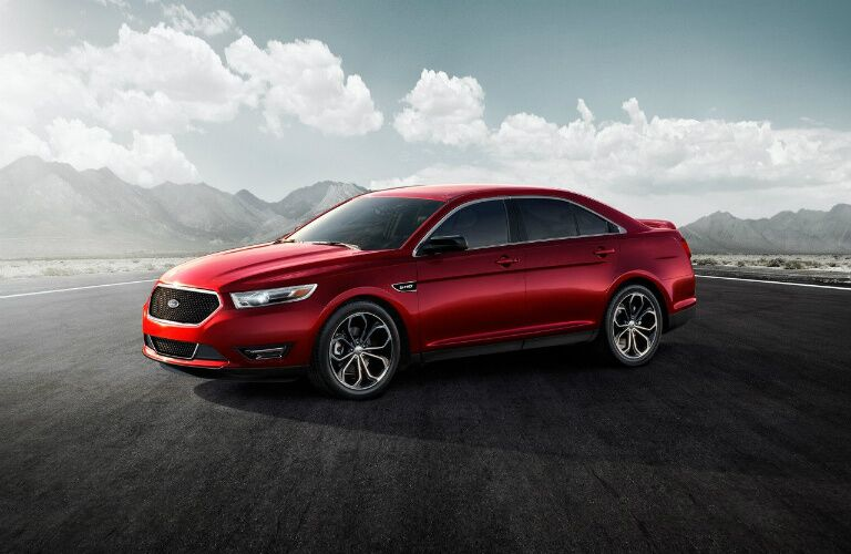 Red 2017 Ford Taurus parked on open road