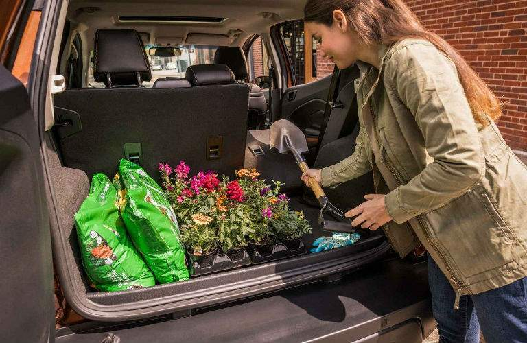 Woman loading gardening equipment into the rear cargo area of the 2018 Ford EcoSport