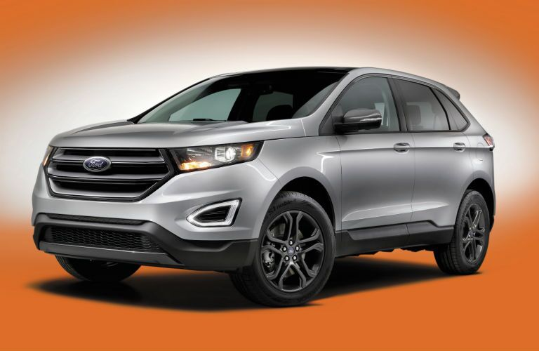Front Quarter profile of the 2018 Ford Edge in front of an orange and white ombre background