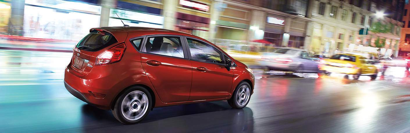 red 2018 Ford Fiesta hatchback driving in city at night