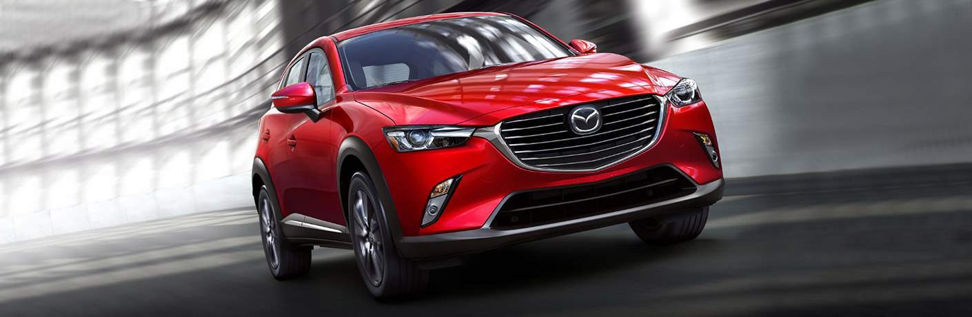 red 2018 Mazda CX-3 driving down a road