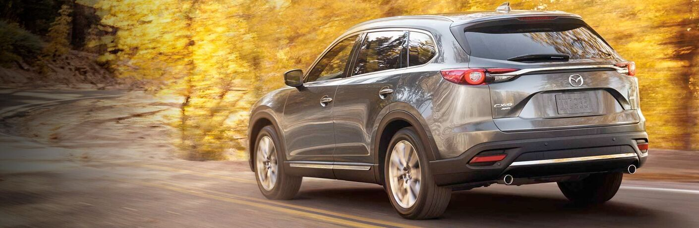 2019 Mazda CX-9 exterior rear shot with gray metallic paint color driving down a winding fall forest road
