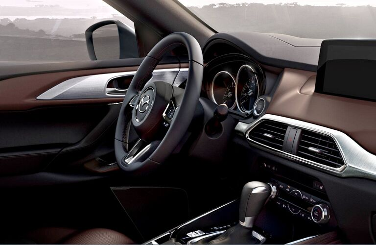 2019 Mazda CX-9 interior close up shot of steering wheel, dashboard design and technology, and transmission knob
