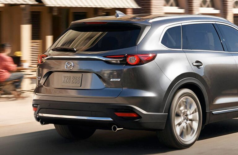 2019 Mazda CX-9 exterior rear shot of back bumper, taillights, and trunk as it drives through the city