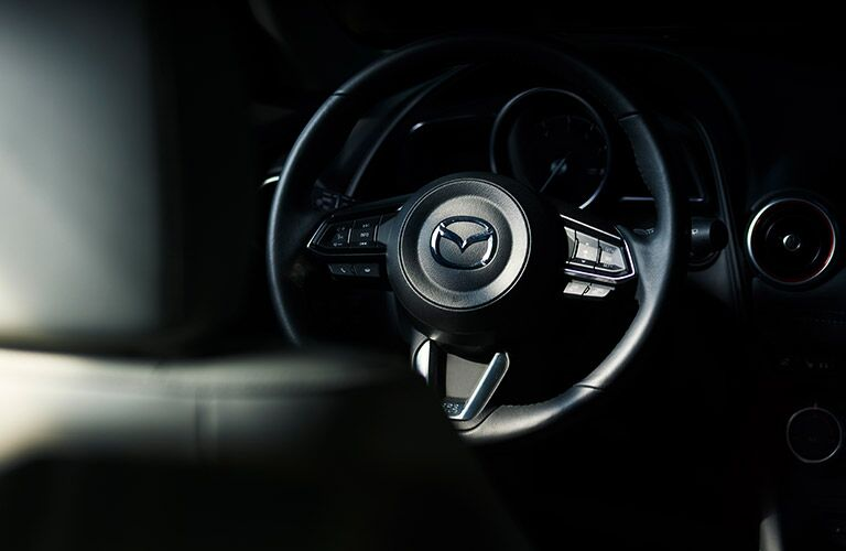 2019 Mazda CX-3 interior closeup shot of steering wheel and Mazda logo brand badge