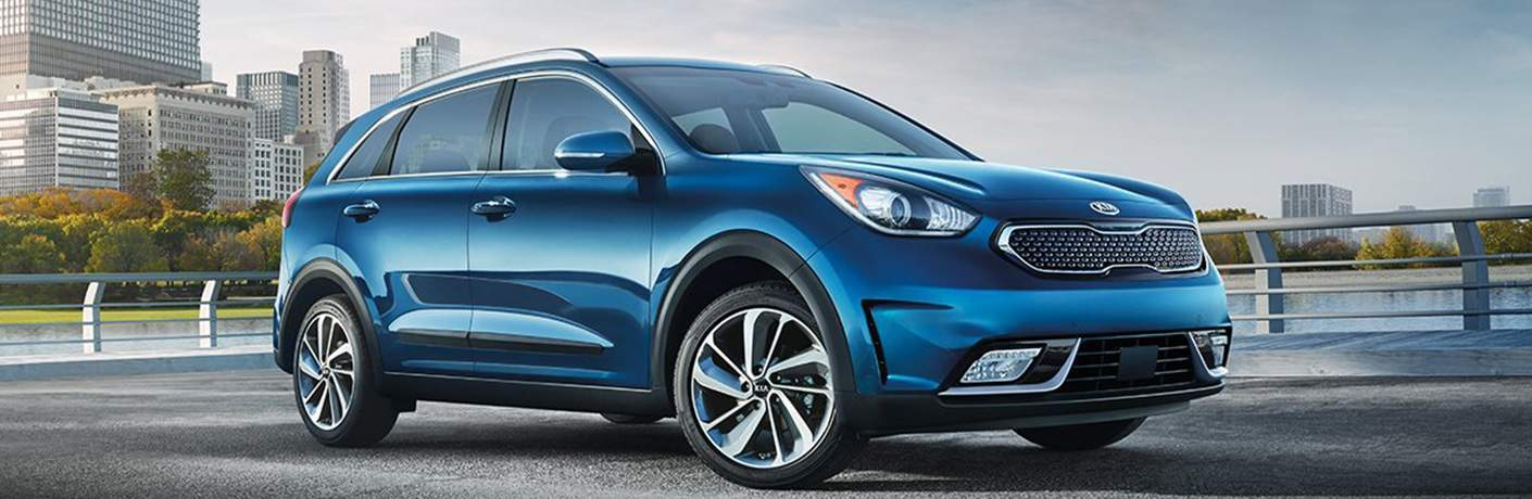 blue 2018 kia niro with river and city skyline behind