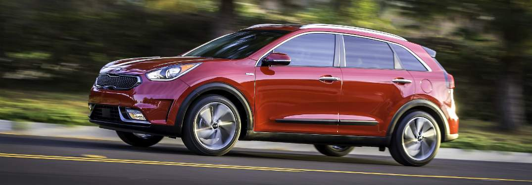 red 2018 kia niro driving up hilly street