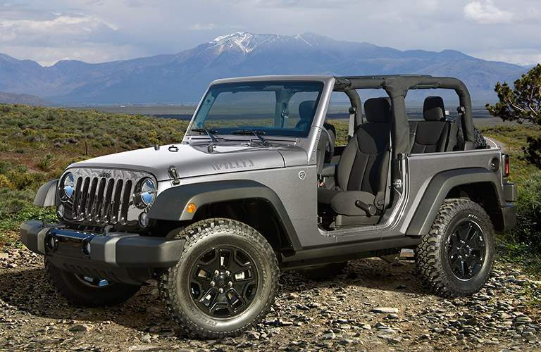 a topless 2017 Jeep Wrangler parked in front of mountains