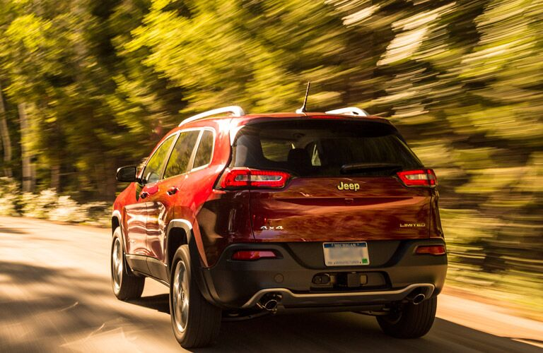 Red 2016 Jeep Cherokee driving away through the forest