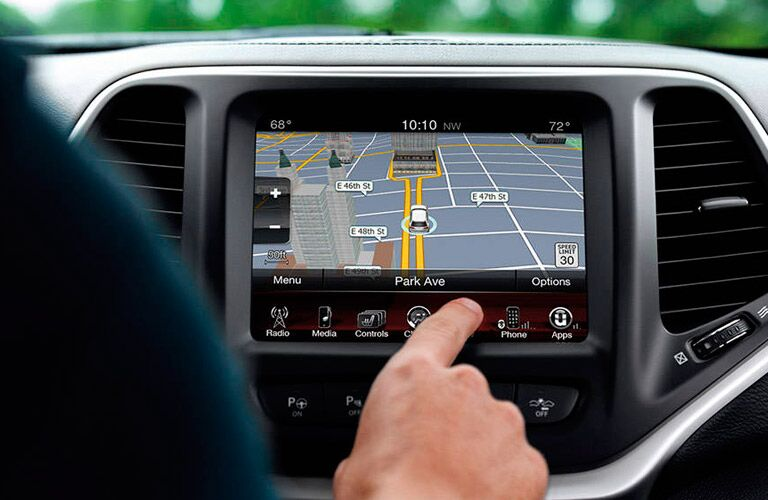 Person using Uconnect on the 2016 Jeep Cherokee