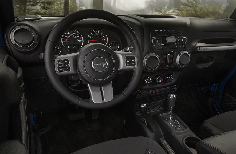 steering wheel and dashboard view of the 2016 Jeep Wrangler Unlimited