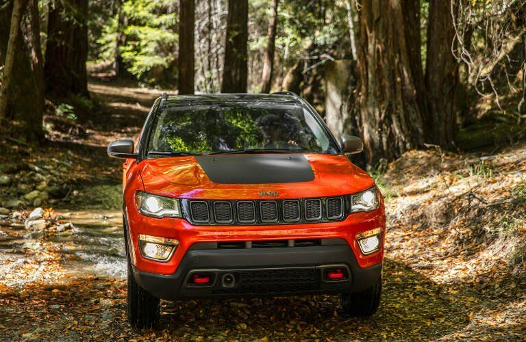 orange 2017 Jeep Compass with bold black hood driving through the woods