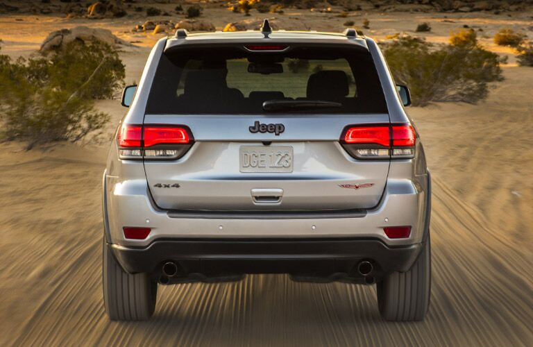 attractive rear view of the 2017 Jeep Grand Cherokee driving on a dirt road in scrubland
