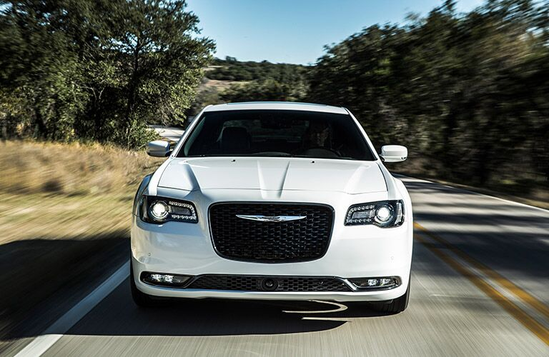 front view of a white Chrysler 300 driving on a road
