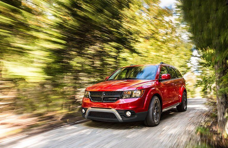 red 2017 Dodge Journey driving through the wood so fast everything else is blurred
