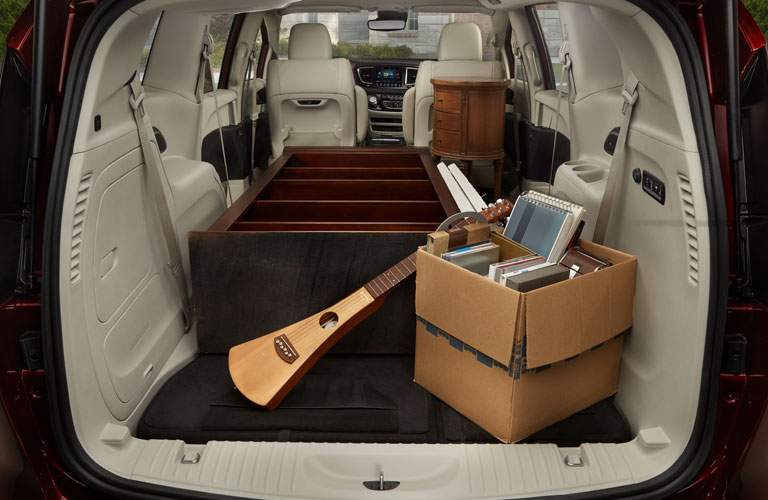 rear storage area of the 2018 Chrysler Pacifica filled with a bookshelf and a musical instrument