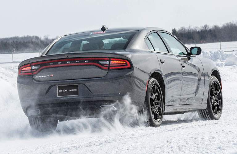 rear view of a grey 2018 Dodge Charger driving in the snow