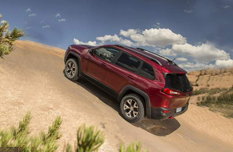 red 2018 Jeep Cherokee driving up a rock face on a blue day
