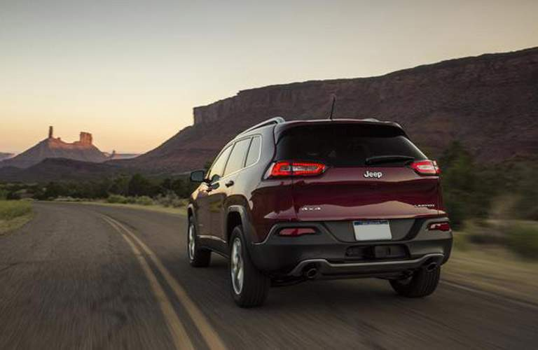 rear view of a purple-ish 2018 Jeep Cherokee driving into the sunset