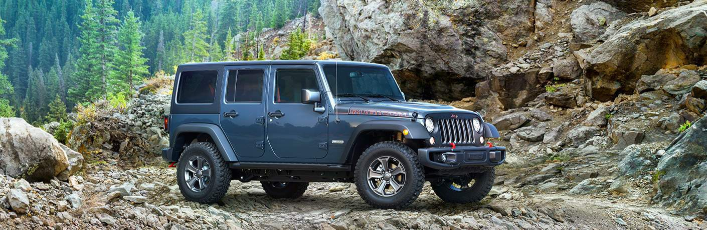 2018 Jeep Wrangler JK Unlimited Rubicon parked in front of rocks and trees