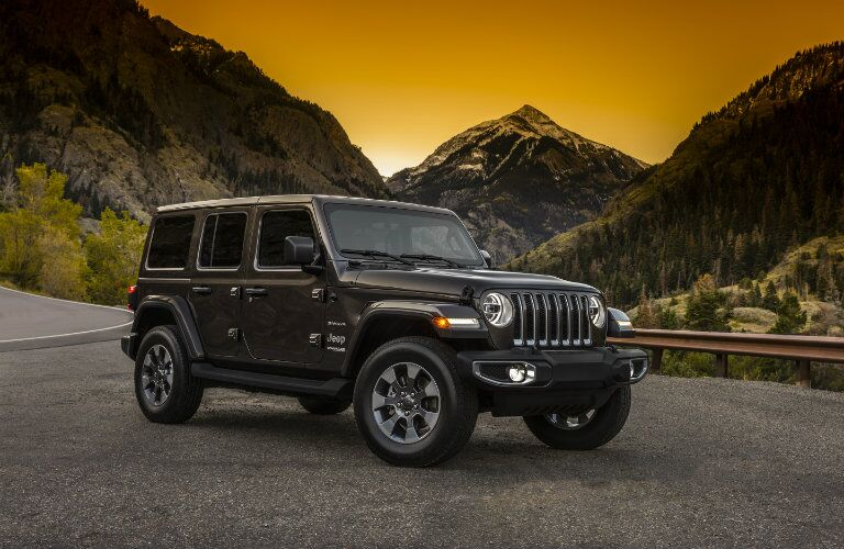 side view of a dark 2018 Jeep Wrangler Unlimited with mountains in the background
