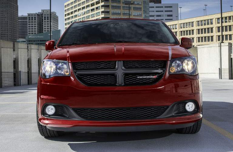 close grille view of a red 2018 Dodge Grand Caravan parked in front of a city