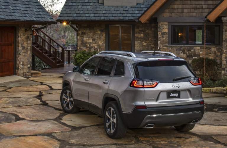 rear and side view of the 2019 Jeep Cherokee parked in front of a rustic house