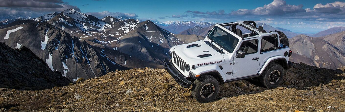 2019 Jeep Wrangler on a mountain with snowy mountains in the background