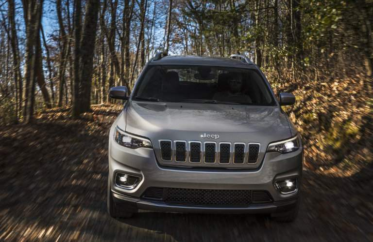front view of the new 2019 Jeep Cherokee driving through the forest