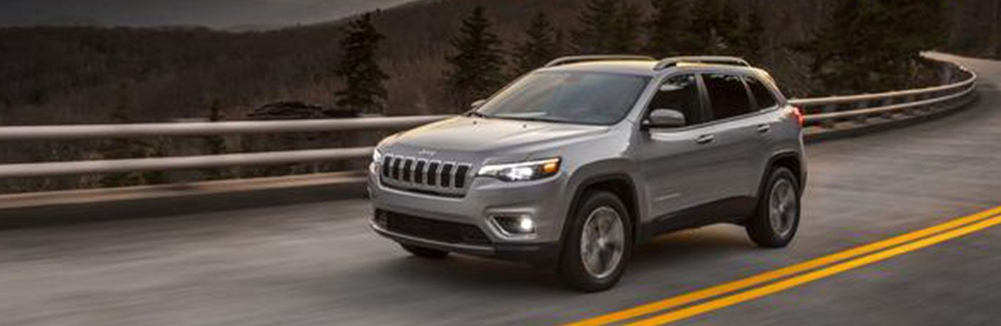 2020 Jeep Cherokee on road in forest landscape