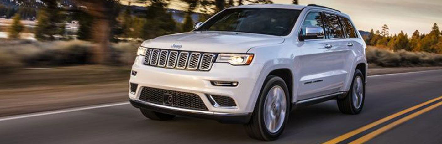 2020 Jeep Grand Cherokee driving down road in forested area