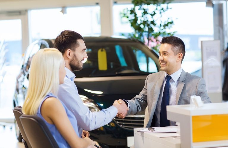 couple shaking hands with salesman