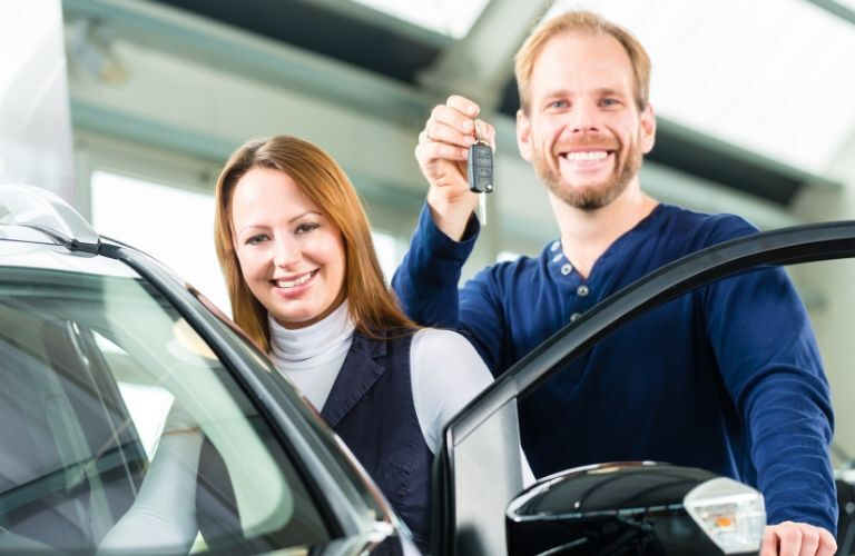 couple with car keys by vehicle