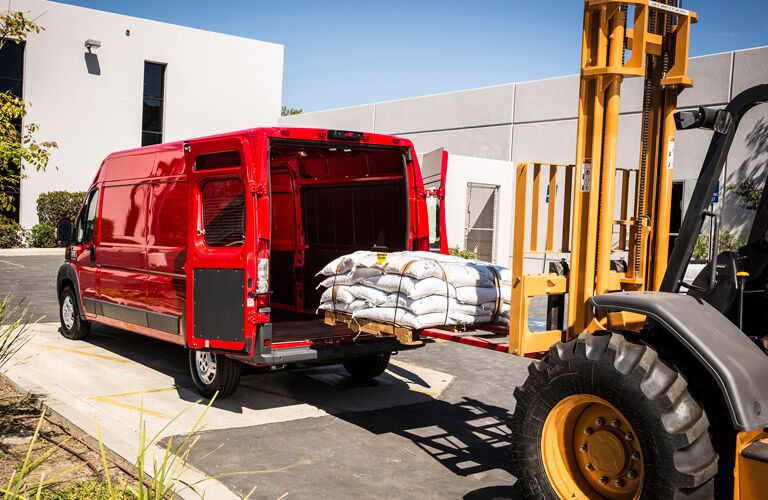 red 2016 Ram ProMaster cargo van being loaded with a forklift
