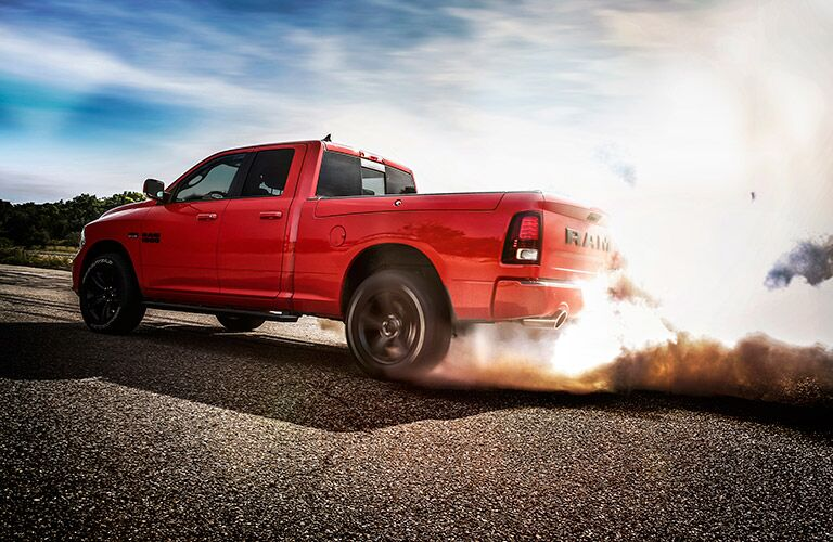 side view of a red 2017 Ram 1500 with dust flying up behind it