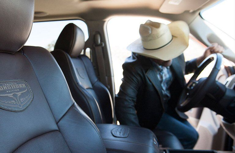 front seats of the 2017 Ram 3500 Laramie Longhorn with a man with a cowboy hat looking at something on the steering wheel