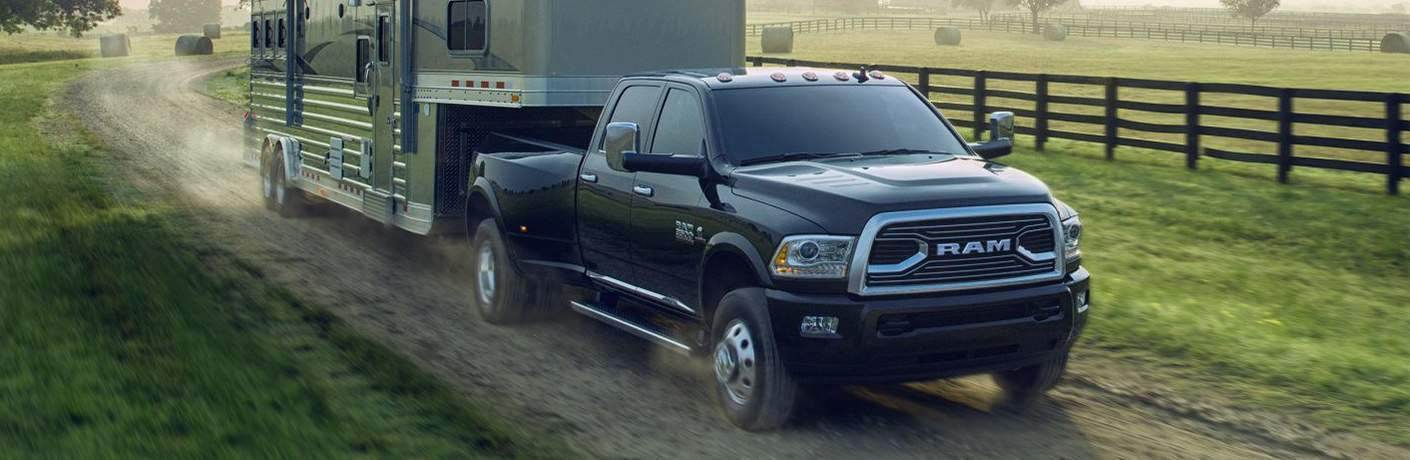 black 2018 Ram 3500 towing a large trailer camper on a dirt road by a farm