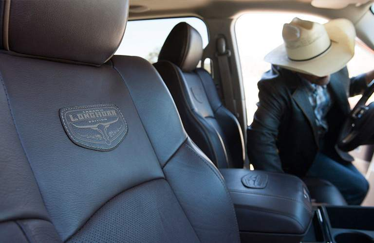 close view of the Laramie Longhorn branding on the front seats of one trim of the 2018 Ram 3500 with a guy with a cowboy hat in the back